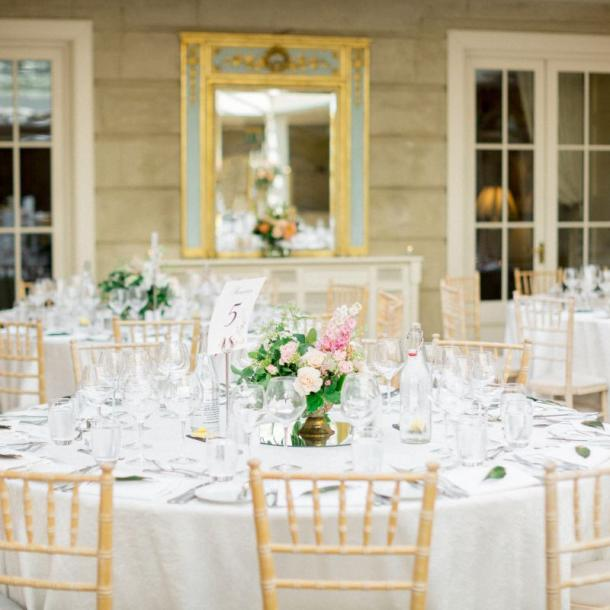 Round tables with crushed cream linens and chiavari chairs. By Christina Brosnan Photography
