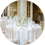 Round Tables with crushed cream linens and chiavari chairs.